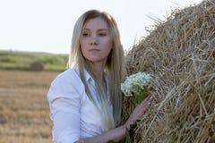 Ung flicka i natur med blommor royaltyfri bild