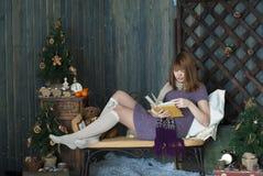 Ung flicka i nytt års inre läsning en bok Royaltyfria Bilder