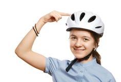 Ung flicka i punkter för en cykelhjälm till en hjälm som isoleras på vit Fotografering för Bildbyråer