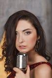 Ung flicka i röd coctailklänning som sjunger med mikrofonen Royaltyfri Foto