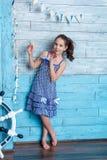 Ung flicka i randig klänning med det marin- nätverket Royaltyfri Bild