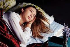 Ung flicka i säng i morgonen med en kopp kaffe Arkivfoto