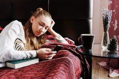 Ung flicka i säng som dricker kaffe och läsning Arkivbilder