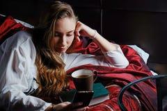 Ung flicka i säng som dricker kaffe och läsning Arkivfoto