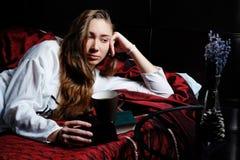 Ung flicka i säng som dricker kaffe och läsning Arkivbild