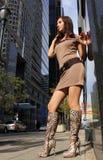 Ung flicka i sexiga kängor som poserar i en stad Royaltyfria Bilder