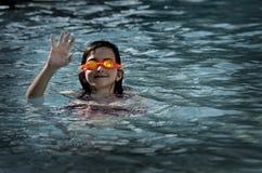 Ung flicka i simbassäng med lyckligt le för skyddsglasögon Fotografering för Bildbyråer