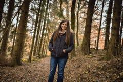 Ung flicka i skogen, le som ser kameran arkivfoton