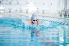 Ung flicka i skyddsglasögon som simmar bröstsimslaglängden royaltyfri bild