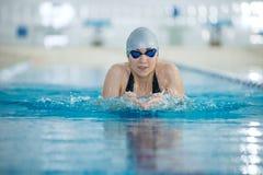 Ung flicka i skyddsglasögon som simmar bröstsimslaglängdstil arkivfoton
