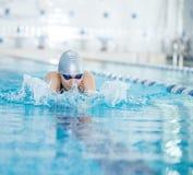 Ung flicka i skyddsglasögon som simmar bröstsimslaglängdstil royaltyfri fotografi