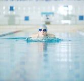 Ung flicka i skyddsglasögon som simmar bröstsimslaglängdstil royaltyfri bild
