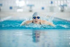 Ung flicka i skyddsglasögon som simmar fjärilsslaglängden arkivbilder