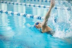 Ung flicka i skyddsglasögon som simmar slaglängden för främre krypande arkivfoton