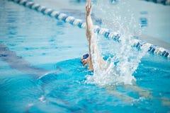 Ung flicka i skyddsglasögon som simmar slaglängden för främre krypande royaltyfri bild