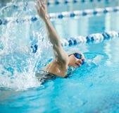 Ung flicka i skyddsglasögon som simmar stil för slaglängd för främre krypande arkivbild