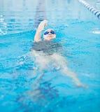 Ung flicka i skyddsglasögon som simmar tillbaka stil för krypandeslaglängd royaltyfri foto