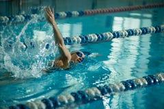 Ung flicka i skyddsglasögon som simmar stil för slaglängd för främre krypande Royaltyfri Bild