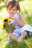 Ung flicka i solros för sommarfältHolding Arkivbild