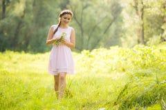 Ung flicka i sommarljusklänning som samlar lösa blommor Arkivbild