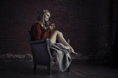 Ung flicka i tröja med den röda koppen kaffe i händer som sitter, i fåtölj och att koppla av Royaltyfria Foton