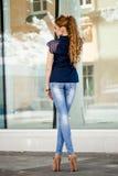 Ung flicka i tröjan som poserar på gatan, ståendelynnet, s Royaltyfri Foto