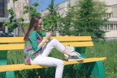 Ung flicka i vit jeans och gymnastikskor som sitter på en gul bänk och bruk en smartphone, online-kommunikation, sociala nätverk, royaltyfria bilder