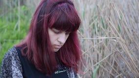 Ung flicka/konstnär/med den burgundy hårteckningen i den öppna luften stock video