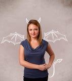 Ung flicka med att dra för för jäkelhorn och vingar Royaltyfri Bild