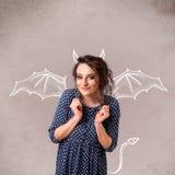 Ung flicka med att dra för för jäkelhorn och vingar Fotografering för Bildbyråer