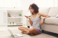 Ung flicka med bärbar datormessaging på mobil royaltyfria bilder