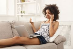 Ung flicka med bärbar datorsammanträde på den beigea soffan arkivfoton