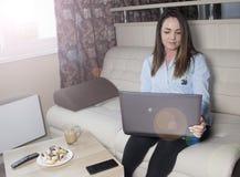 Ung flicka med bärbara datorn och telefonen Royaltyfria Bilder