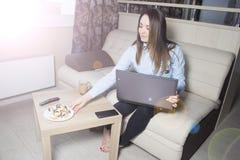 Ung flicka med bärbara datorn och telefonen Royaltyfri Foto