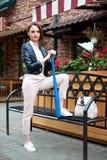 Ung flicka med baseballslagträet som poserar nära gatakafét arkivfoton