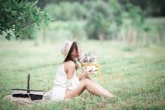 Ung flicka med blommor i sommarhatten som poserar på fält Royaltyfria Foton