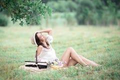 Ung flicka med blommor i sommarhatten som poserar på fält Royaltyfri Fotografi