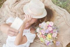 Ung flicka med blommor som gör selfie på fält Royaltyfri Foto