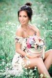 Ung flicka med blommor som poserar på fält Arkivfoto