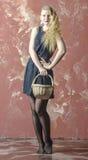 Ung flicka med blont lockigt hår i en lång klänning med prickwiiiiiiiiiiith en korg Arkivbild