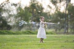 Ung flicka med bubblatrollstaven Royaltyfri Foto