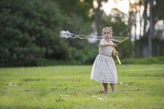 Ung flicka med bubblatrollstaven Arkivfoto