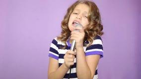 Ung flicka med dans för mikrofon för lockigt hår hållande sjungande och funy, stock video