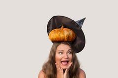 Ung flicka med den förskräckta framsidan och halloween pumpa på hennes huvud Royaltyfri Foto