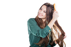 Ung flicka med den isolerade hårborsten leende Fotografering för Bildbyråer