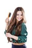 Ung flicka med den isolerade hårborsten leende Royaltyfria Foton