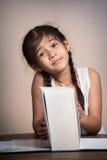 Ung flicka med den stora boken Fotografering för Bildbyråer