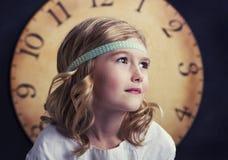 Ung flicka med den stora tappningklockan royaltyfria foton