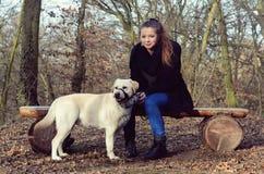 Ung flicka med den vita hunden Arkivfoto