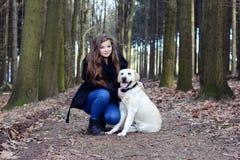 Ung flicka med den vita hunden Arkivbild